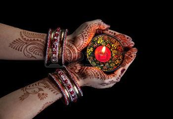 38632550-mãos-da-mulher-com-vela-exploração-henna-isolado-no-fundo-preto-com-trajeto-de-grampeamento
